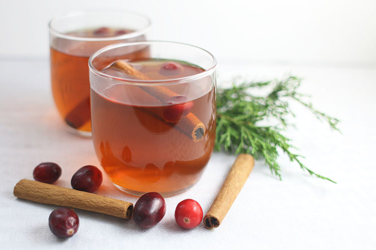 Clear Glasses of Instant Pot Hot Spiced Apple Cider with Cranberries and Cinnamon Sticks