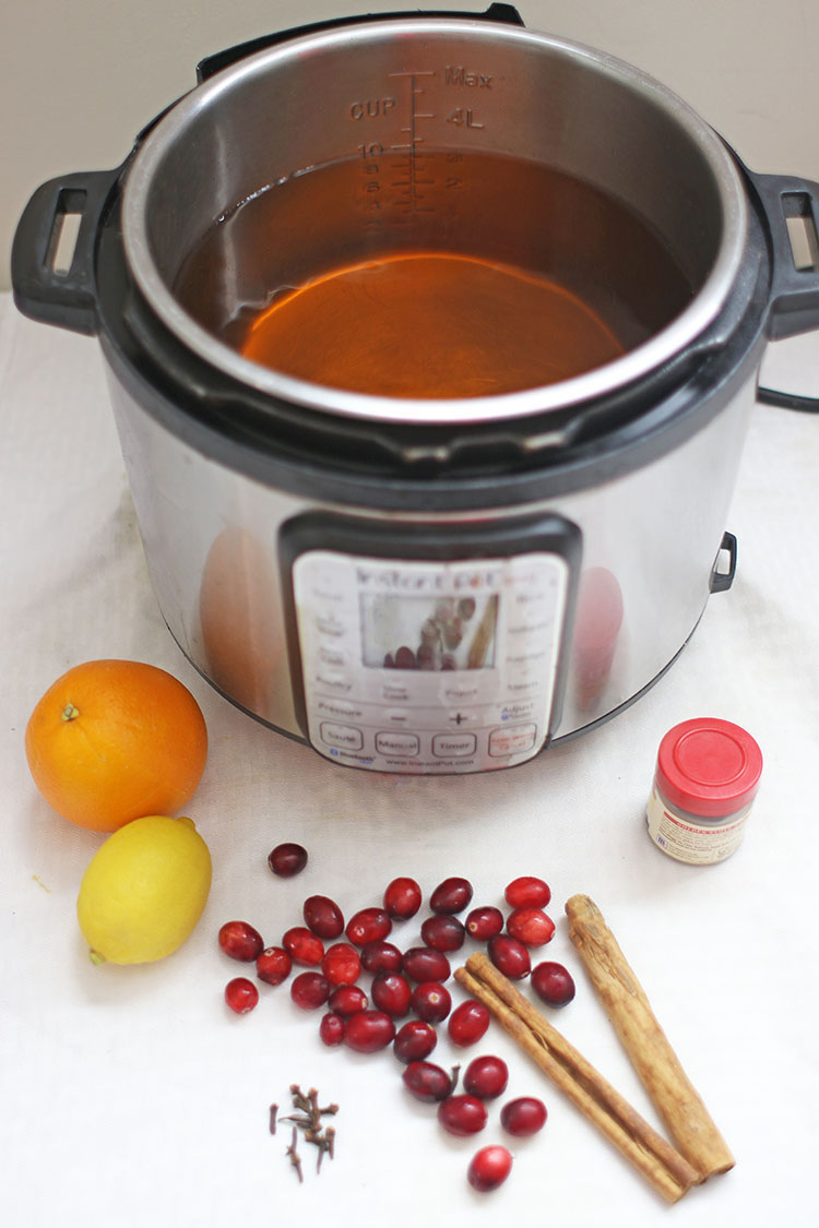 Instant Pot with apple juice and other ingredients for Hot Spiced Apple Cider