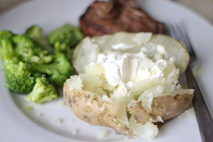 Instant Pot Baked Potatoes with butter and sour cream on plate with broccoli and steak